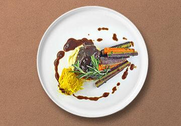 Geschmorte Ochsenbäckchen auf Selleriepüree mit bunten Karotten und gelben Möhrensalat
